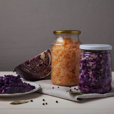 A cut red cabbage next to a jar of pickled red cabbage and a jar of pickled white cabbage