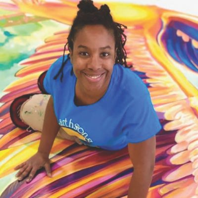 Tia Richardson kneeling on a mural