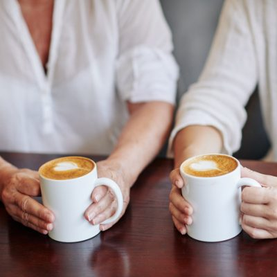 two women drink coffee together at a table