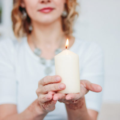 Woman in white dress holding a burning candle