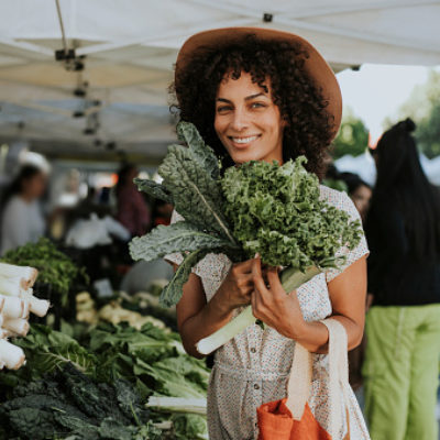 Woman buying kale at a farmers market