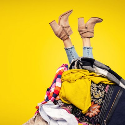 woman's legs sticking out of pile of clothes