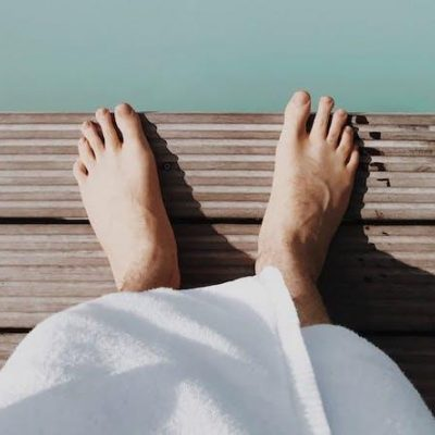bare foot in robe by blue water