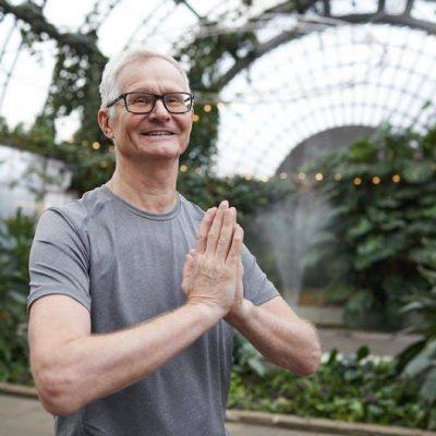 man holding palms together saying namaste