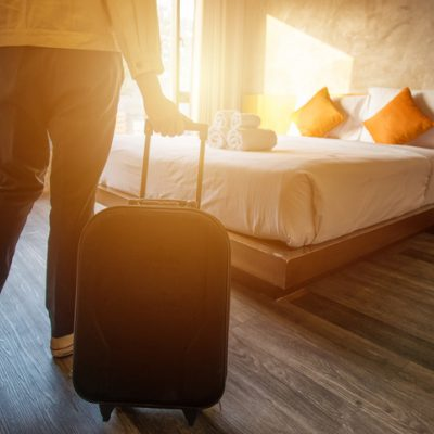 person with suitcase arriving in room at retreat