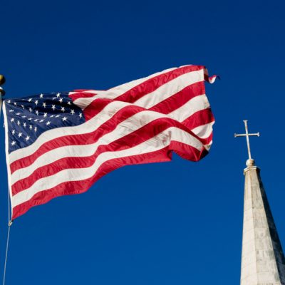 American flag flying in front of church