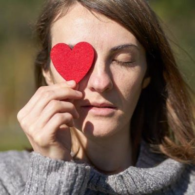 woman holding heart-shaped paper cut out over her eye