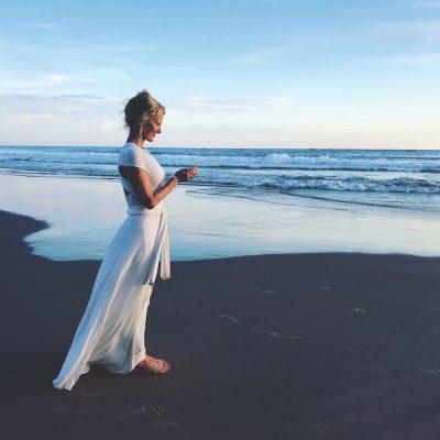 Shiva Rea on beach in white dress