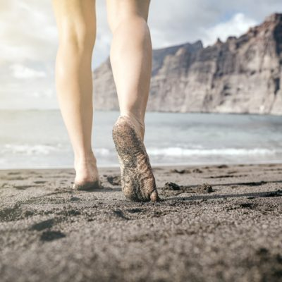 woman walking on the beach barefoot to stay grounded