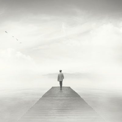 Man standing on foggy dock