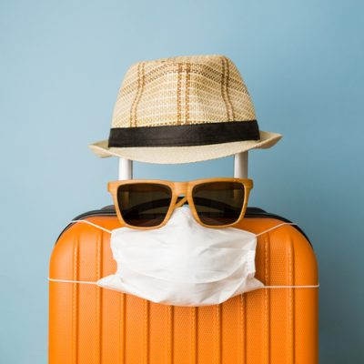 suitcase with sunglasses, mask, and hat