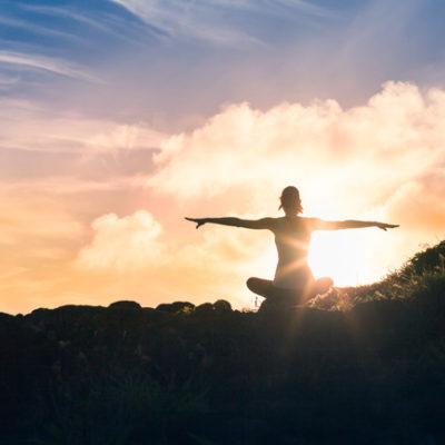 woman doing yoga poses at sunrise