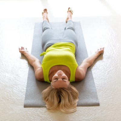 woman laying on mat yoga nidra transitional