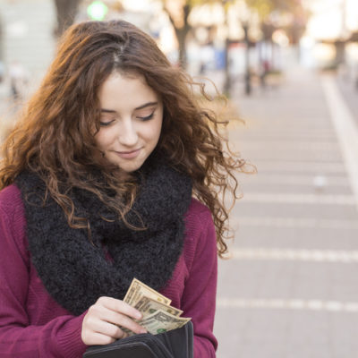 young woman shopping and taking out money from wallet on street