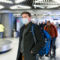 Man in gray coat wearing protective disposable medical mask in airport during spread of N-CoV 2019 influenza coronavirus