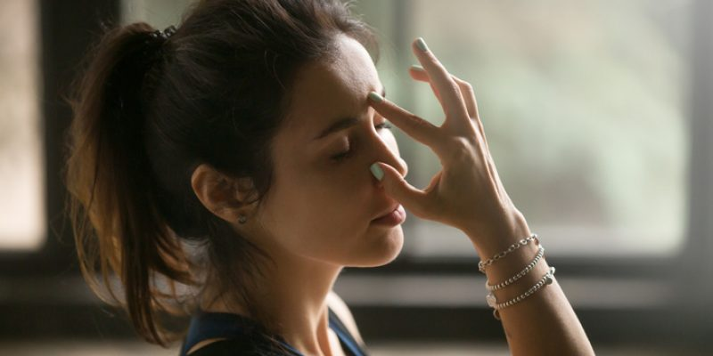 Woman doing yoga using alternate nostril breath technique
