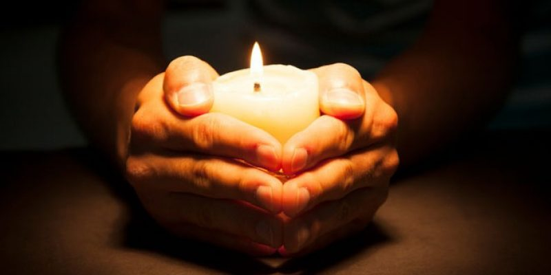 Pair of hands holding candle