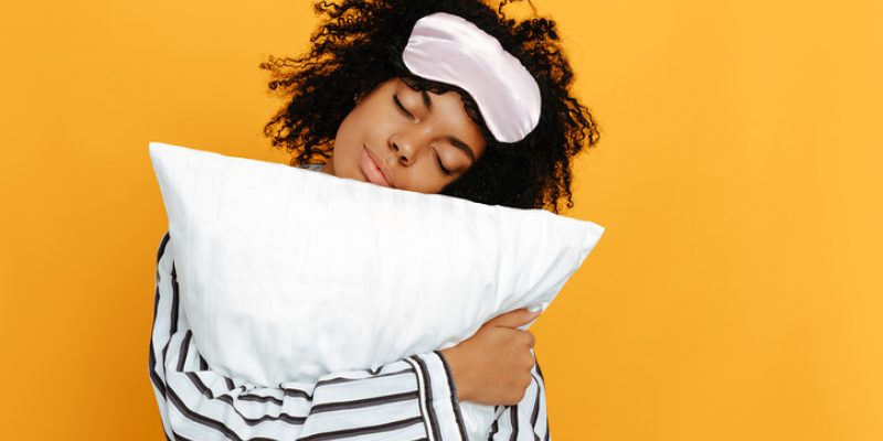 Young woman in pajamas is hugging a pillow, on a yellow background.