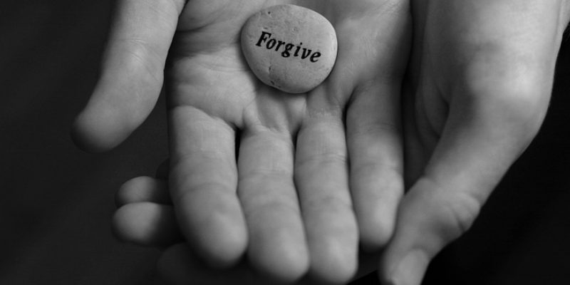 """A hand holding a smooth stone that reads """"forgive."""""""