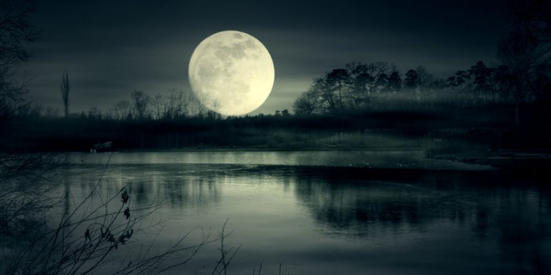 A moon rising above a lake.