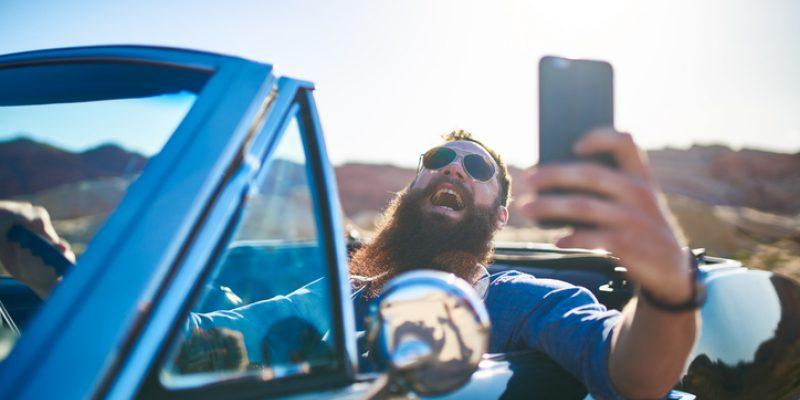 bearded man taking selfie while driving car