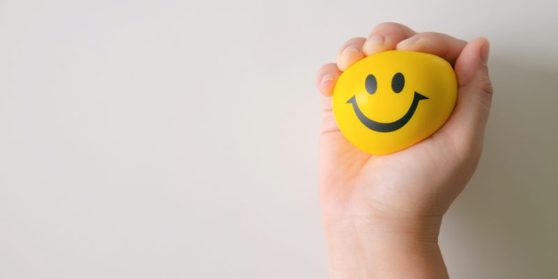 The positivity plague, hand squeezing smiley face stress ball