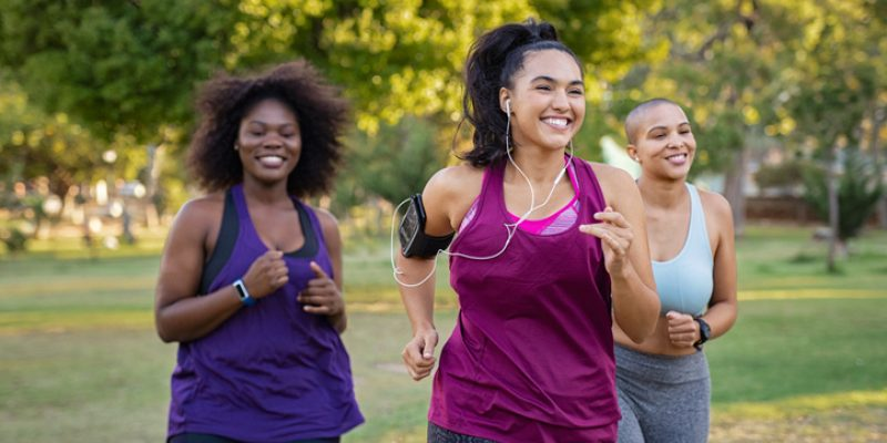 Group of female friends jogging together at park.