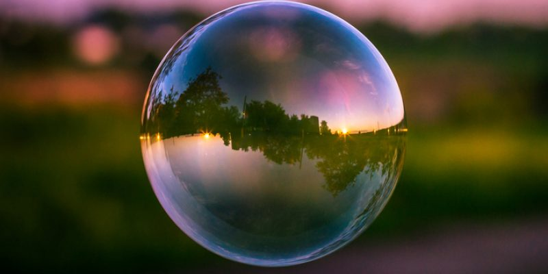 Reflection of a colorful sunset sky inside a soap bubble