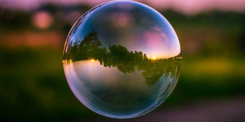 Reflection of a colorful sunset sky inside a soap bubble