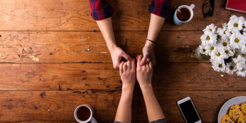 Couple holding hands with coffee at table