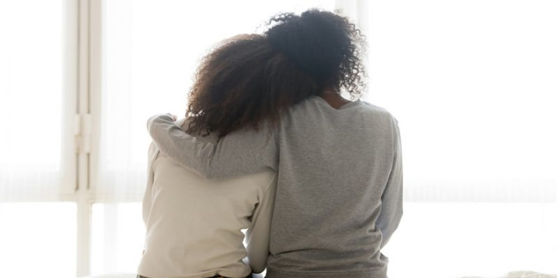 Back view of loving mom hugging teen daughter