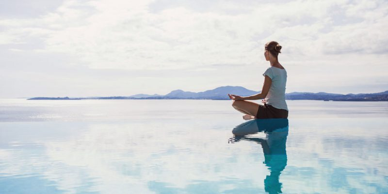 Calm scene of woman meditating on water