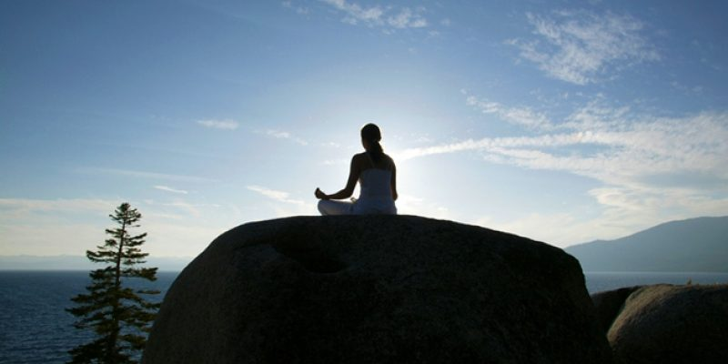 Woman meditating on large rock