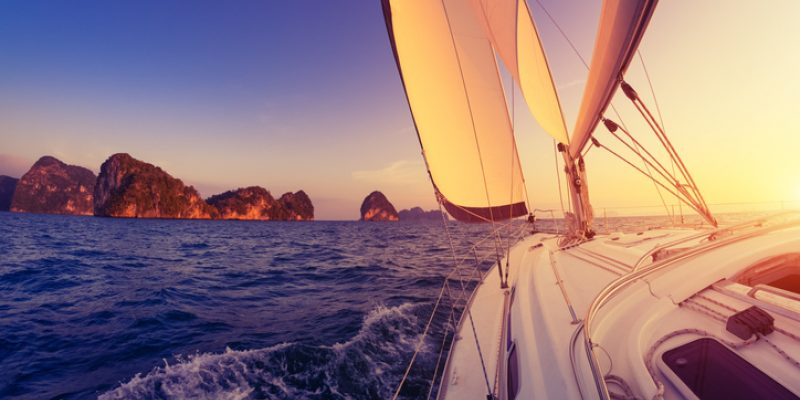 A sailboat sails toward a rocky island