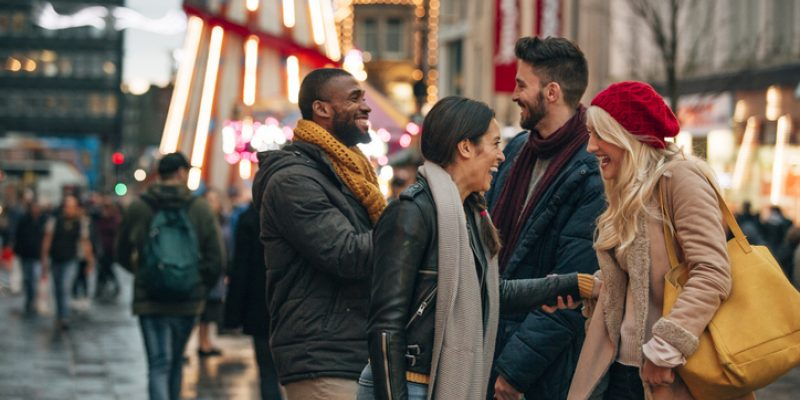 Side view of two couples meeting on a city street. It's winter and there is a fair ground ride on the street.