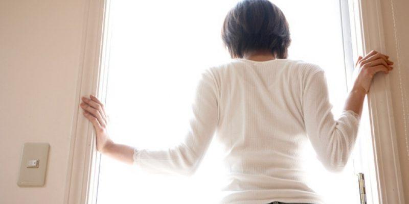Woman standing in bright doorway