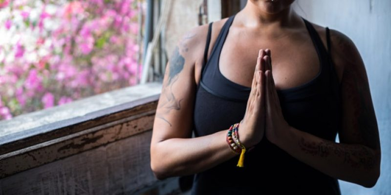 Woman with tattoos holds hands in anjali mudra
