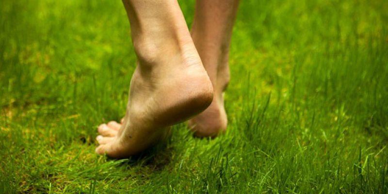 Man walking barefoot on grass