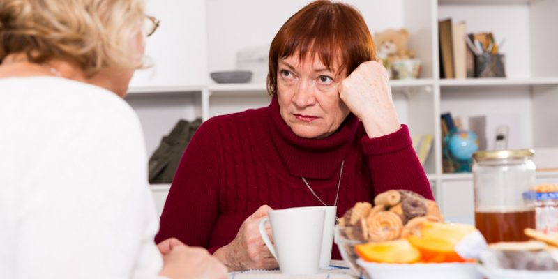 Stressed looking woman having coffee with her friend