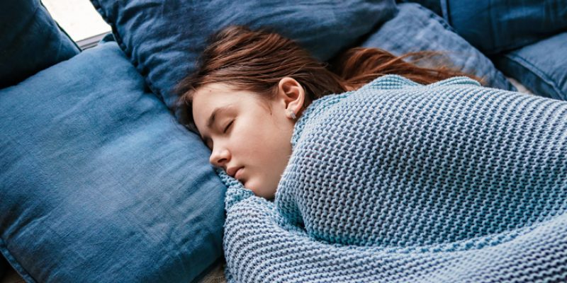 Girl with the winter blues in her bed with blue pillows and bedsheets