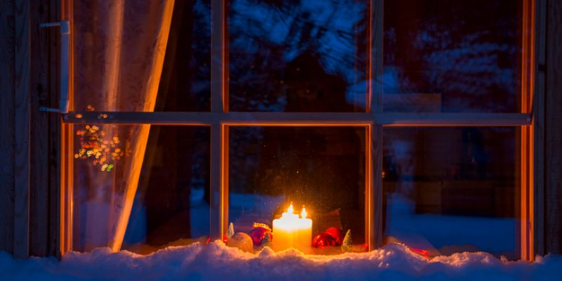 A candle burns in the window of a home on a snowy evening.