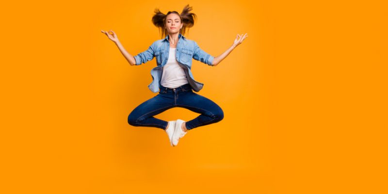 woman in meditation pose joyfully is in the air