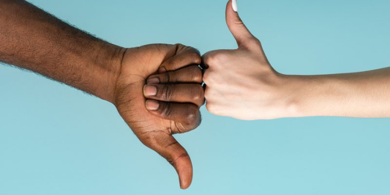 masculine and feminine hands giving thumbs up and thumbs down for saying no