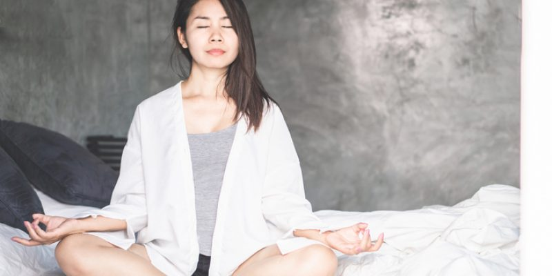 Beautiful Asian woman taking deep breaths with prenatal yoga