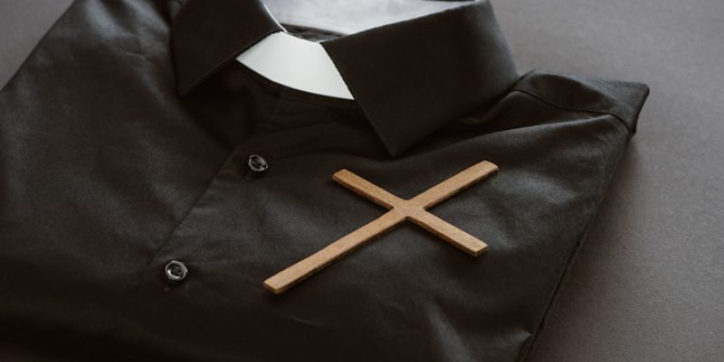 An empty priest's shirt with a cross and priest collar.