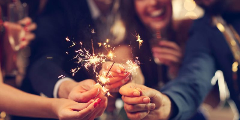Happy people celebrating with sparklers
