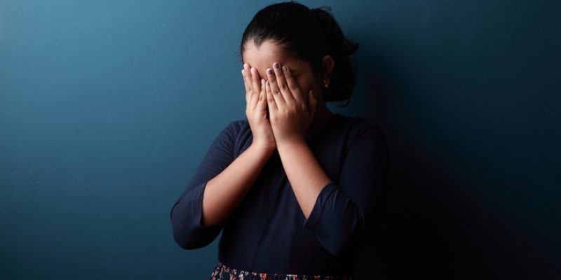 young girl covering her face in shame