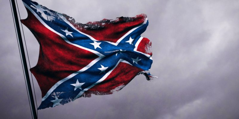 Closeup of ripped, torn, grungy, old waving Confederate flag of the national states of america, US