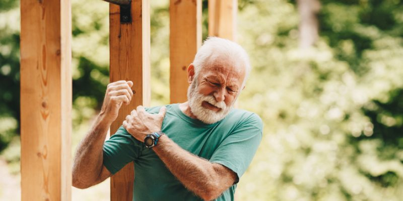 Spiritual meaning of right shoulder pain man holding shoulder