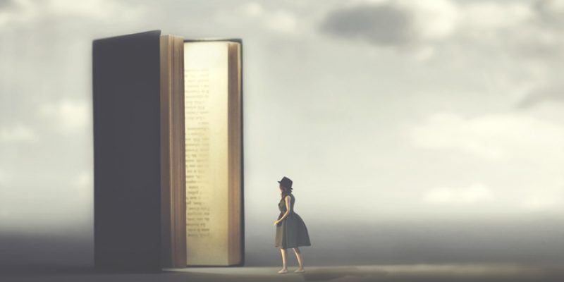 Surreal book opens a door illuminated to a woman, enjoying spirtuality and books.